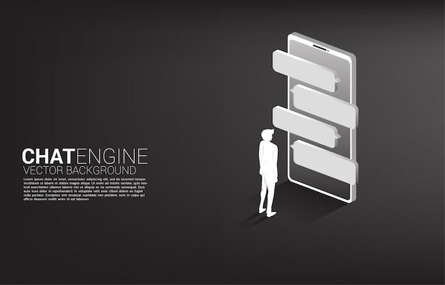 携帯電話でバブルのスピーチで立っているシルエット実業家。チャットボットエンジンと通信。