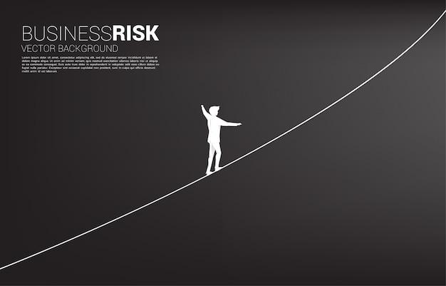 ロープの散歩道を歩くビジネスマンのシルエット。ビジネスリスクとキャリアパスの概念