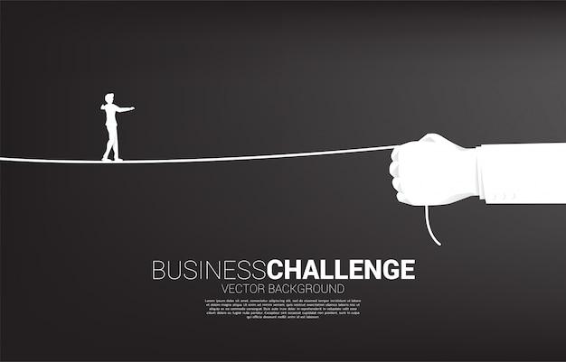 ビジネスマンのシルエットは、ビジネスマンの手でロープを歩きます。ビジネスチャレンジとキャリアパスの概念。