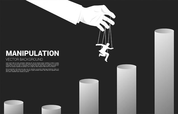 高いグラフにジャンプする実業家のシルエットを制御する操り人形マスター。操作とマイクロ管理の概念