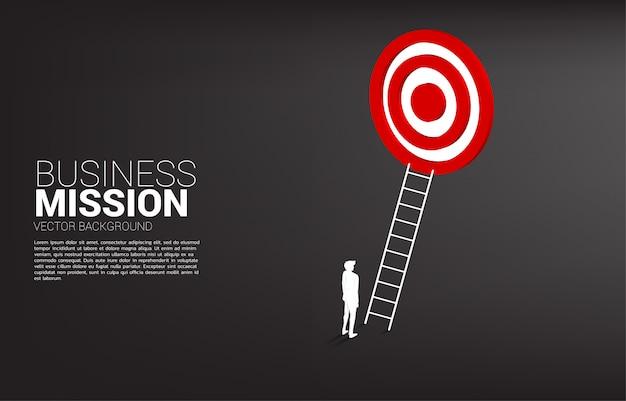 Силуэт бизнесмена с лестницей для целевого дартс. концепция видения миссии и цели бизнеса