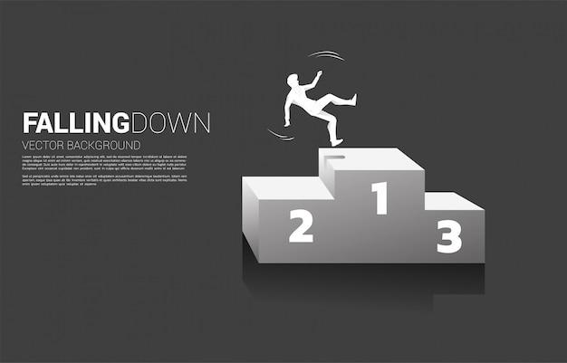 表彰台から落ちてくるビジネスマンのシルエット。失敗と偶発的なビジネスのコンセプト