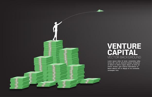 Силуэт бизнесмена выбросить деньги банкноты оригами бумажный самолетик из стека денег. бизнес-концепция начала бизнеса и предпринимателя