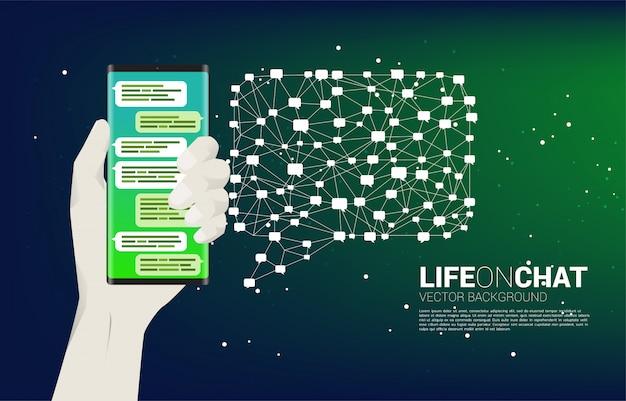 Побеседуйте на мобильном телефоне в руке с концепцией предпосылки речи пузыря полигона для социальных темы и новостей.