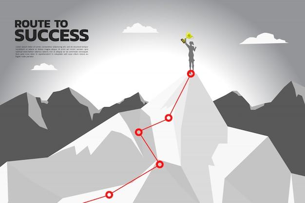 Путь к успеху. силуэт бизнес-леди с чемпионским трофеем на вершине горы.