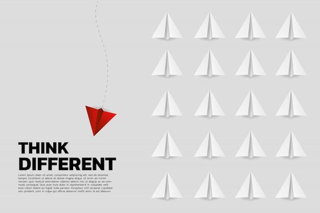 Красный оригами бумажный самолетик идет другим путем из группы белых