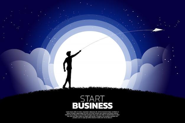 ビジネスマンのシルエットは、折り紙の紙飛行機を夜に捨てます。起業と起業家のビジネスコンセプト