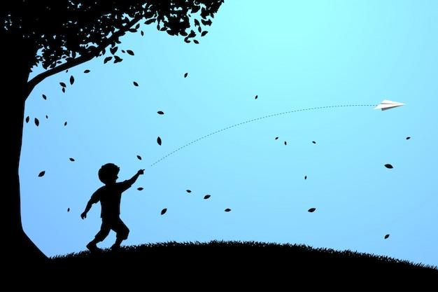 折り紙の紙飛行機を捨てるために走っている少年。