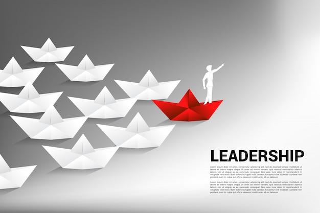 ビジネスマンは赤い折り紙の紙の船に前方を向く