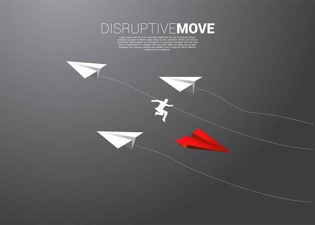 ビジネスマンのシルエットは折り紙紙飛行機からジャンプします。