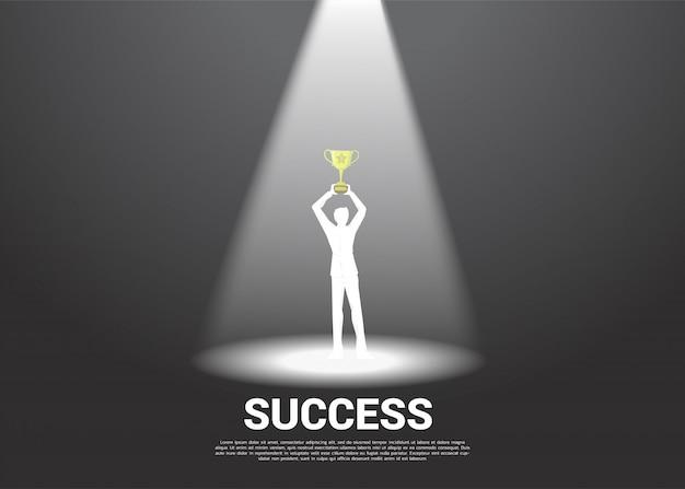 Силуэт бизнесмена с золотым трофеем в центре внимания.