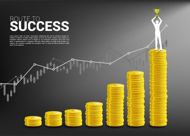 コインのスタックを持つ成長グラフの上に立っている勝者トロフィーを持ったビジネスマンのシルエット。