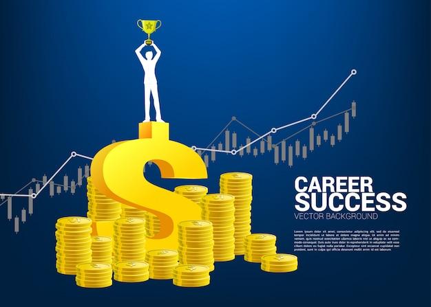 コインのスタックを持つ成長グラフの上に勝者トロフィー立っているビジネスマンのシルエット