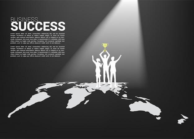 Силуэт бизнесмен и предприниматель с чемпионский трофей, стоя на карте мира