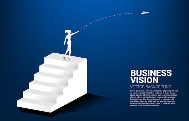 Силуэт бизнесмен бросить самолет оригами на вершине лестницы