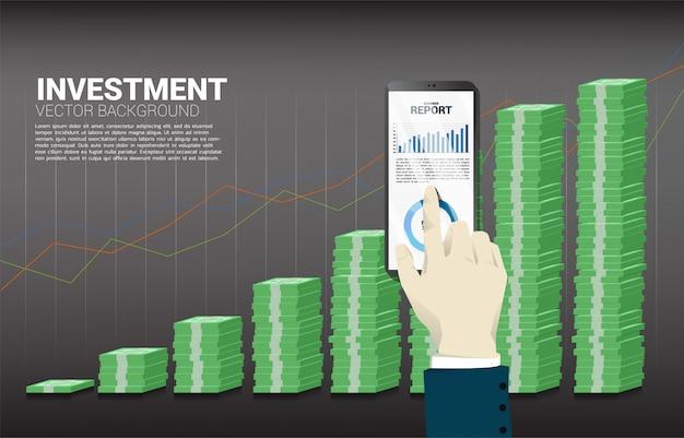 紙幣と良いビジネスグラフの背景のスタックを持つビジネスマン手タッチ携帯電話