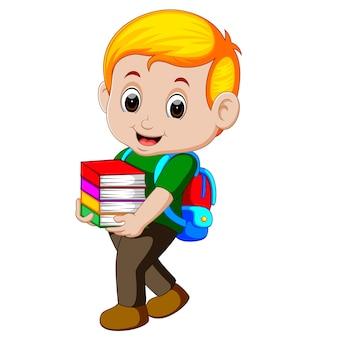 バックパック付きの本の山を抱いている漫画の少年