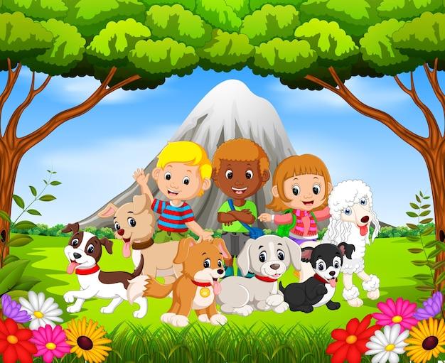 Дети и их домашние собаки в парке с горной сценой