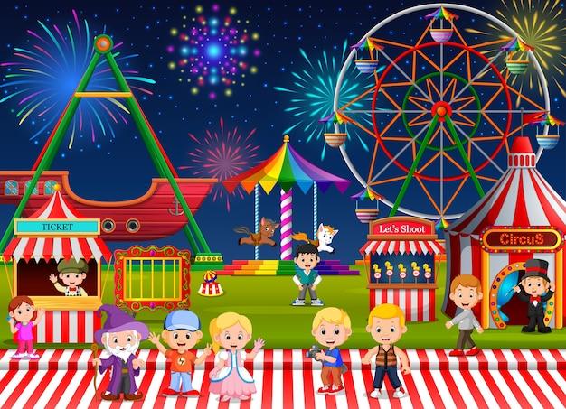 夜に遊園地で楽しむ多くの子供たちと人々の労働者