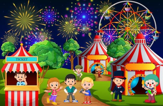 夜に遊園地で楽しむ多くの子供と人々の労働者