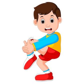 彼の膝の上に傷を抱えている男の子