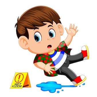 濡れた床に滑っている少年