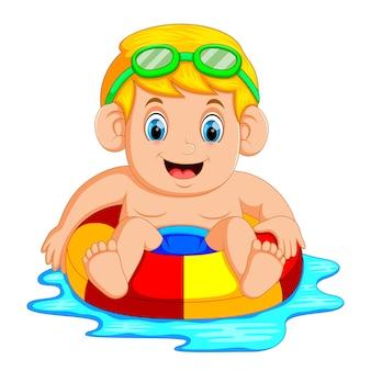 スイミングプールでカラフルなインフレータブルリングで遊んでいる少年