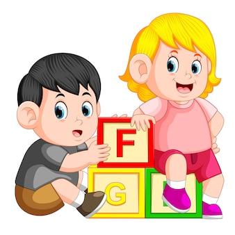 アルファベットブロックで遊んでいる子供たち