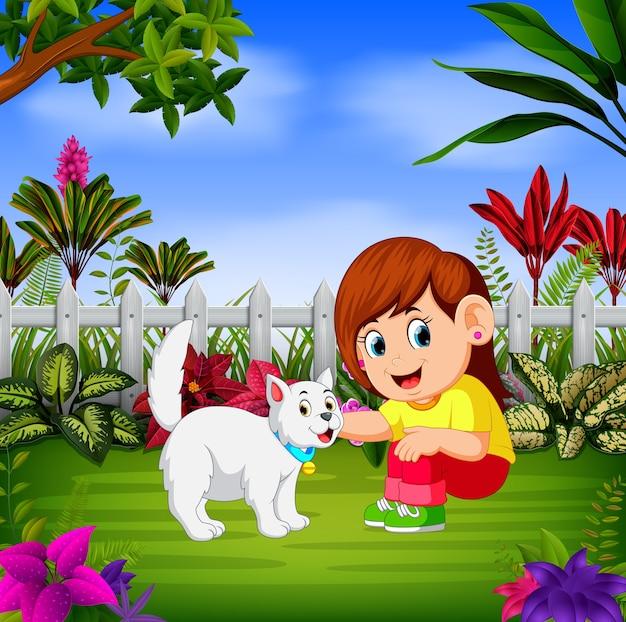 美しい女の子がフェンスの近くで彼女の猫と遊ぶ