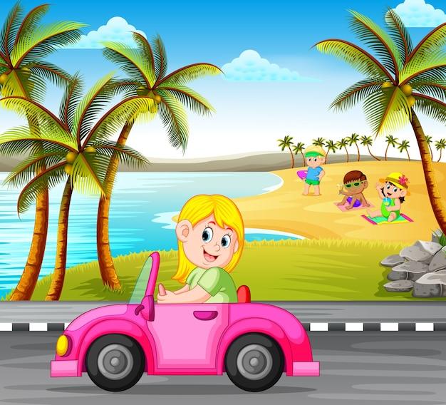 女は、美しいビーチの背景と通りのピンクの車を運転する