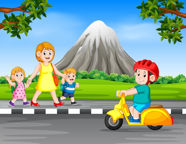 女性と子供たちが道路を歩いているときにオートバイを運転する少年
