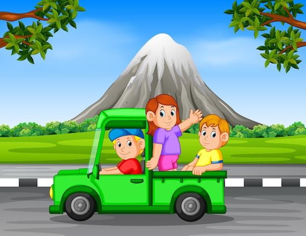 美しい岩の山の背景で車の中を振って幸せな家族