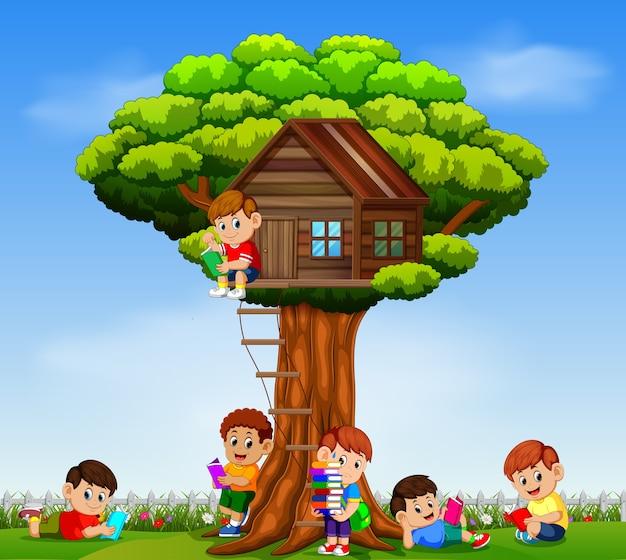木の家の庭で本を読んで遊んでいる子供たち