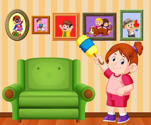 美しい少女は彼女の家のダスターでフレームの写真をきれいにする