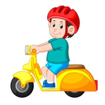 男は黄色のベスパ・オートバイに乗って、赤いヘルメットを使います