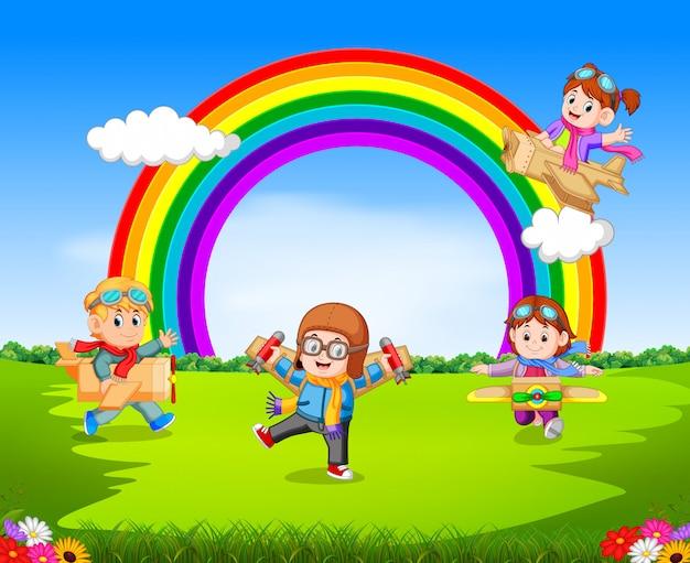 屋外で段ボール飛行機で遊んでいる幸せな子供たち