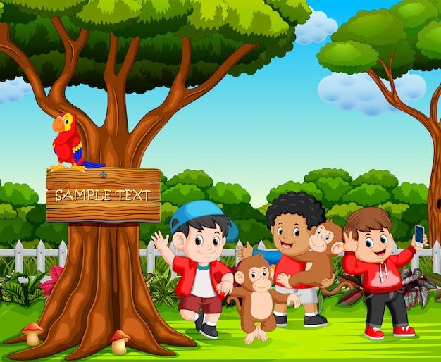 幸せな子供と美しい自然の中で遊んでいる猿