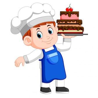 若いシェフはケーキでトレイを持っています