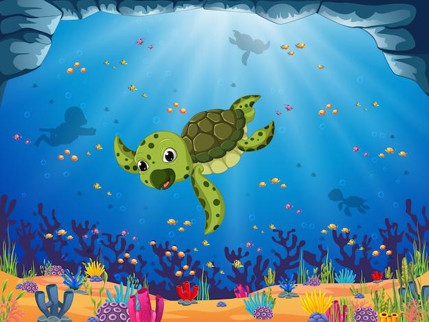 青い海の景色の下で若いアオウミガメが泳いでいます。