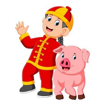 小さな男の子が中国の新年に大きなピンクのブタと遊んでいます。