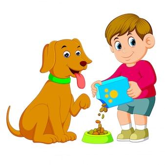 小さな男の子は彼の大きな茶色の犬のために食べ物を与えています。