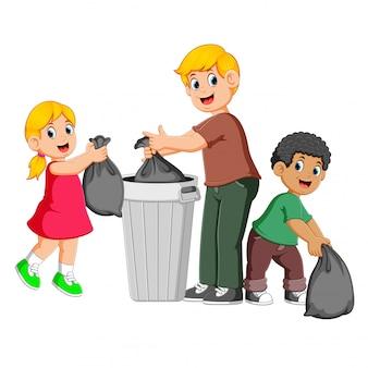 Отец и его дети выбрасывают мусор