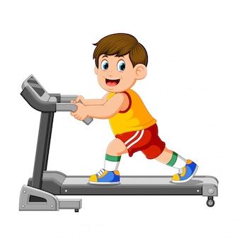 Молодой человек в спортивной одежде работает на беговой дорожке