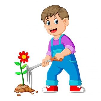 Молодой человек заботится о растениях и использует грабли