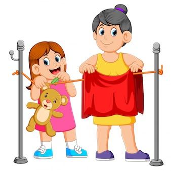 Маленькая девочка помогает повесить белье ее мать