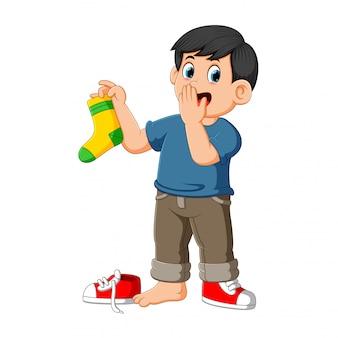 男は臭い靴下を保持している指で鼻をグリップします。