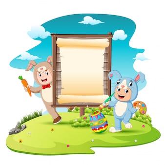 幸せな子供たちのバニー衣装を着て、空白の看板の背景を持つ卵の絵