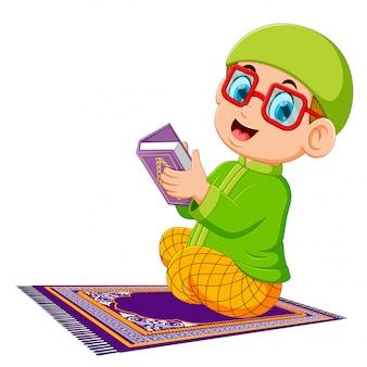 赤い眼鏡を使用している少年はアルコーランを保持しています。