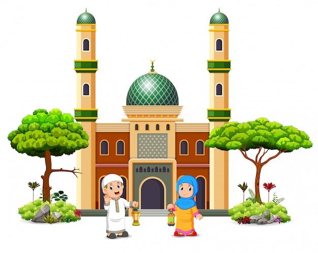 男の子と女の子は緑のモスクの前にラマダンランタンを持っています。