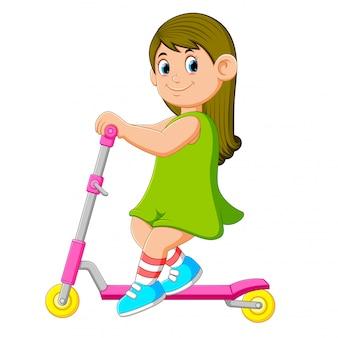 緑色のドレスの女の子がスクーターで遊んでいます。
